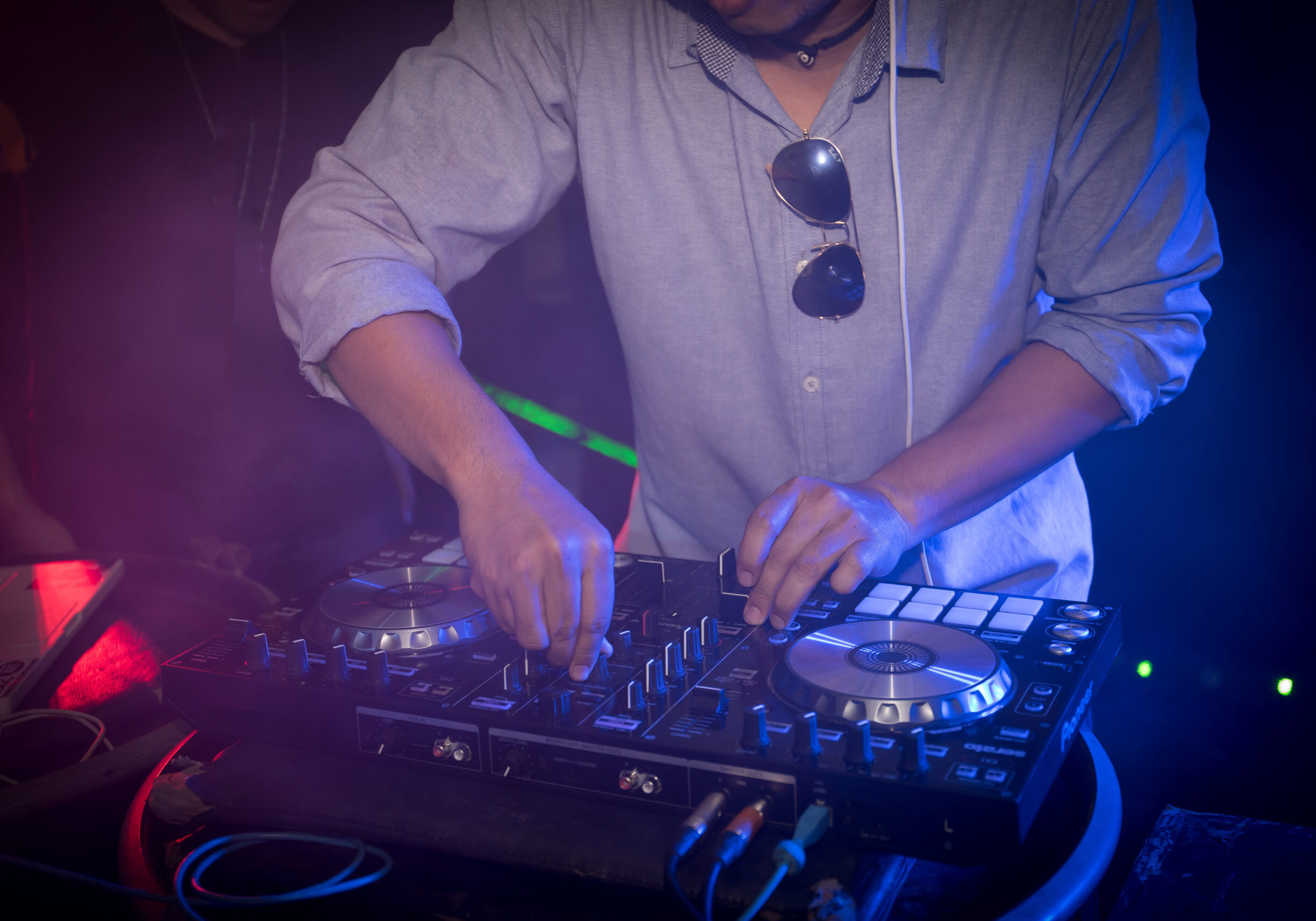 DJ playing turntable music on night club party