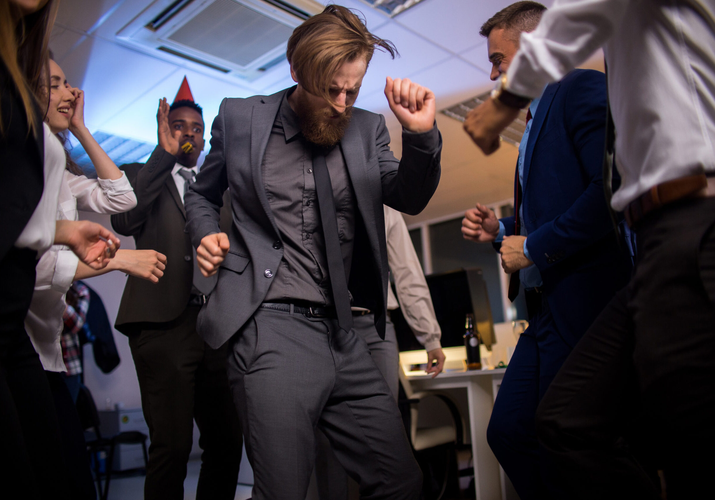 Low angle view of male office worker in elegant suit dancing with colleagues on  corporate party